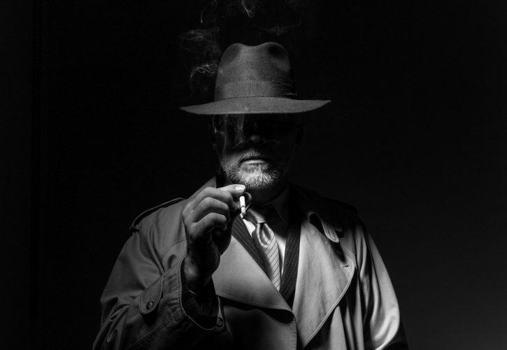 Raucher als Film-noir-Charakter mit Trenchcoat und Hut